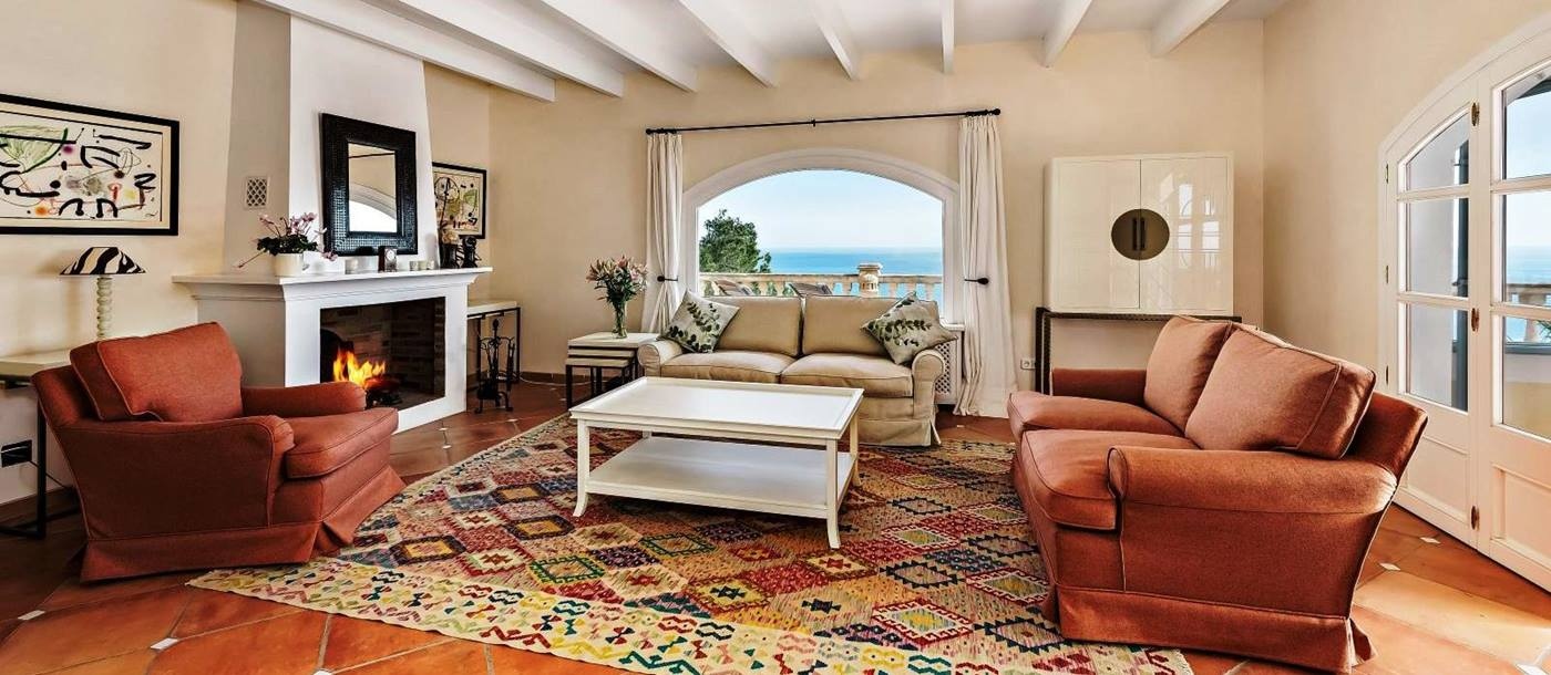 sitting room with 3 sofas and square white coffee table in front of fireplace at villa canyamel in Mallorca, spain