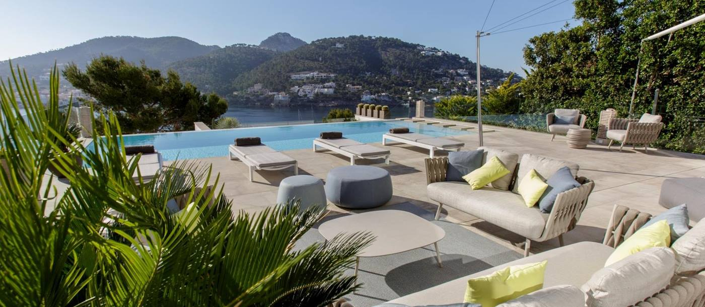 Terrace with sofas, armchairs, coffee tables, sun loungers, pool, trees and port view at Villa Infinitum, Mallorca, Spain