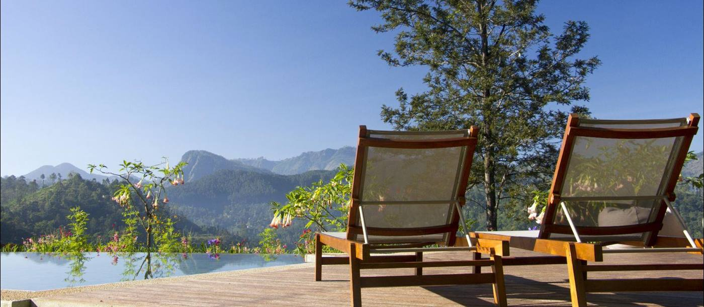 Two sunloungers on a sun deck surrounded by trees and flowers with mountains in the background at Nine Skies in Sri Lanka