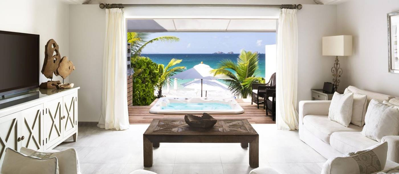 A living room suite with white furniture with a view out onto the beach at Hotel Cheval Blanc in St Barths