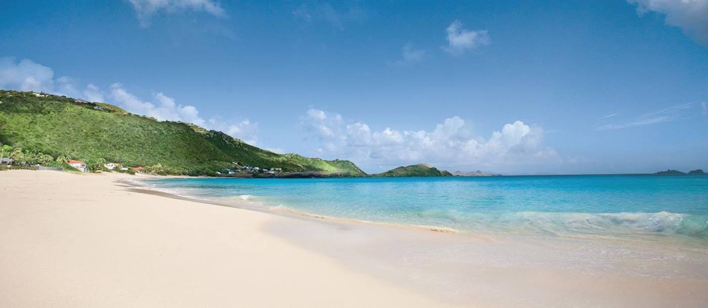 A view of the beach with white sands and blue sky at Hotel Cheval Blanc in St Barths