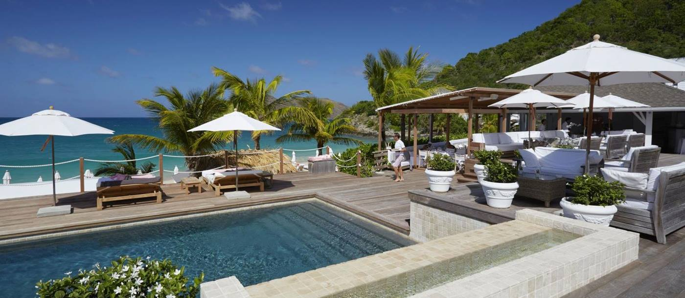 The white bar at Hotel Cheval Blanc in St Barths with chairs, tables and sun umberellas around a pool