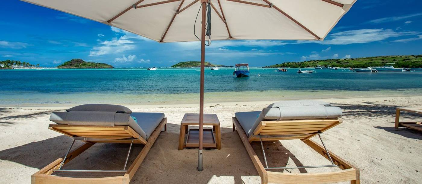 Two sun loungers under a sun umberella on the beach at Le Barthelemy Hotel & Spa in St Barths