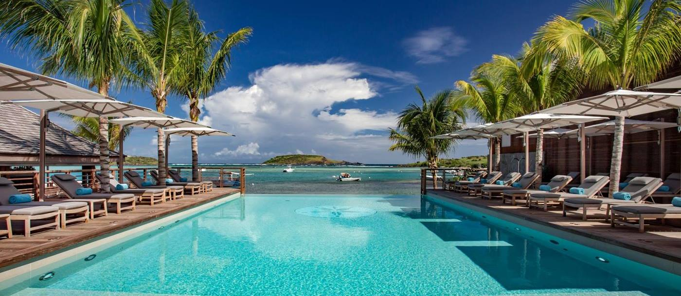 A view down the pool to the sea with sun beds and palm trees either side at Le Barthelemy Hotel & Spa in St Barths