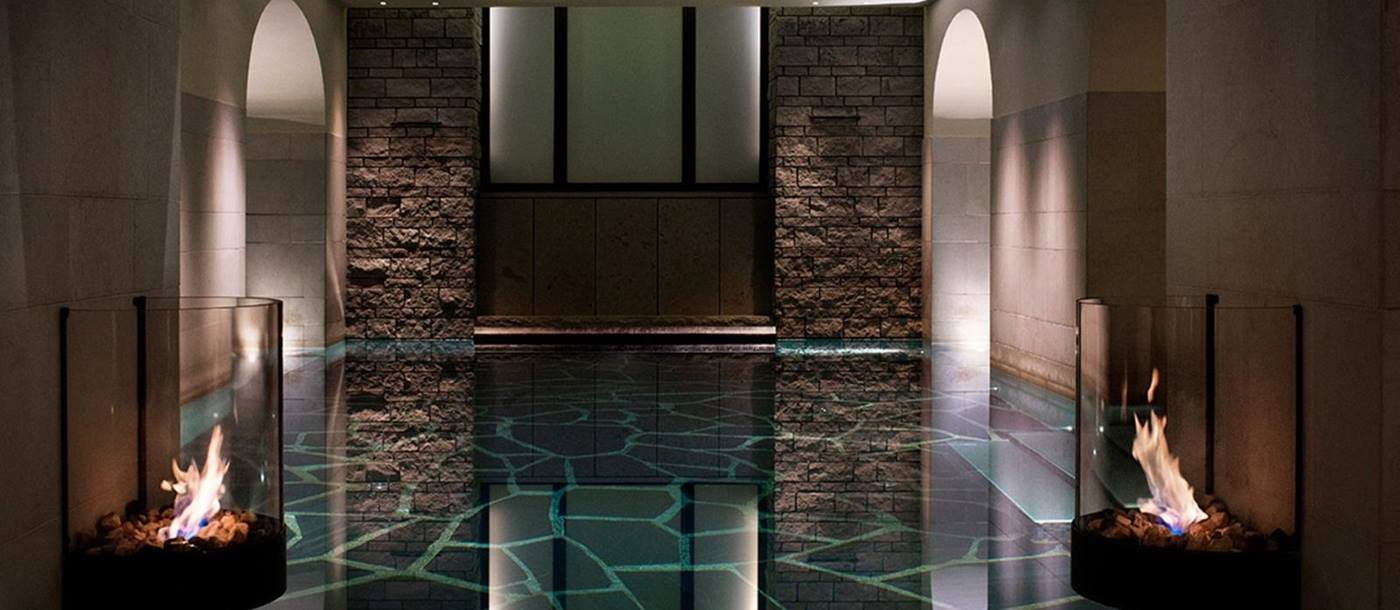 Indoor pool with mood lighting and fire in glass bowls