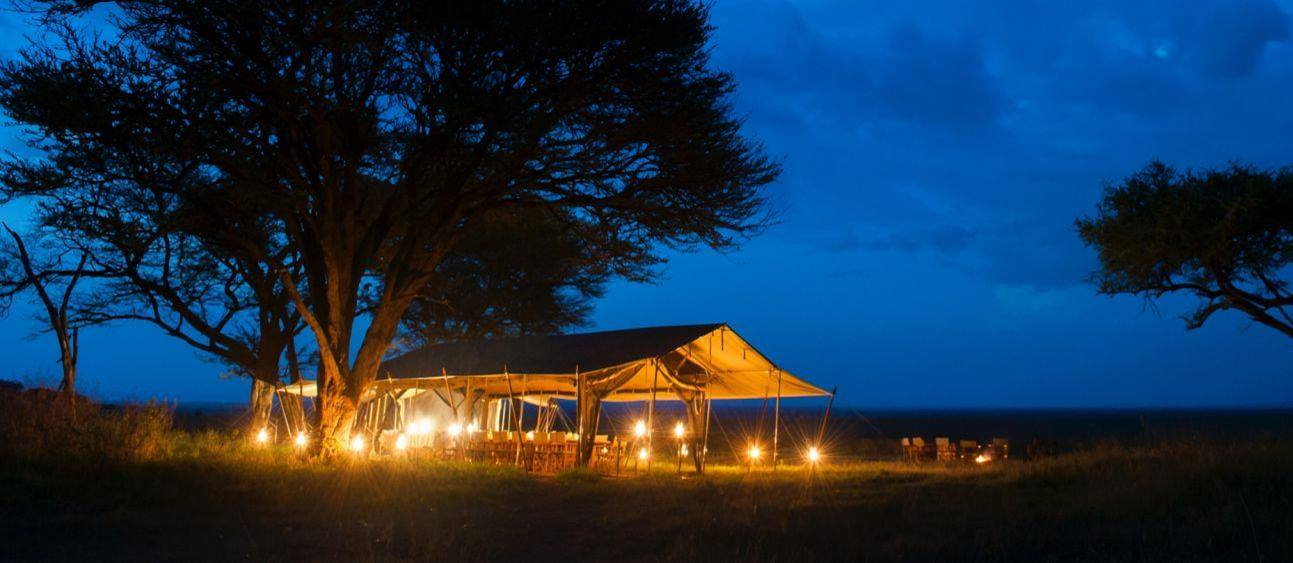 Dining tent at night at Serengeti Safari Camp in Tanzania