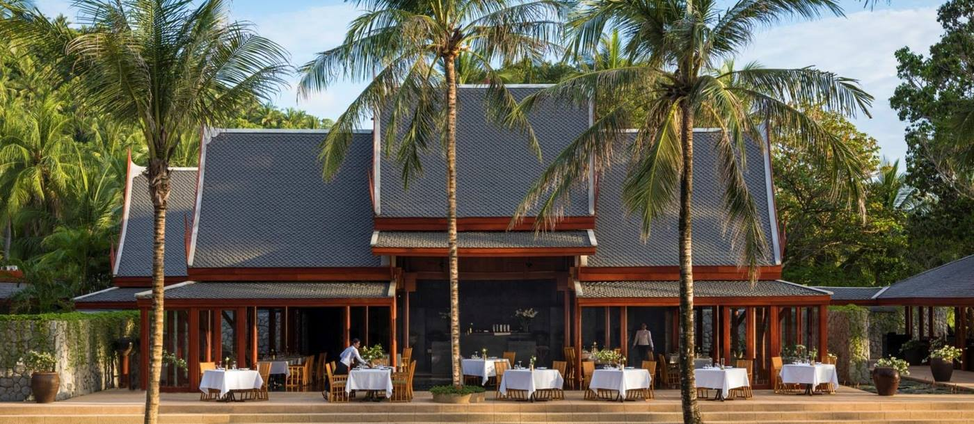 Main restaurant with outdoor seating and pool at Amanpuri