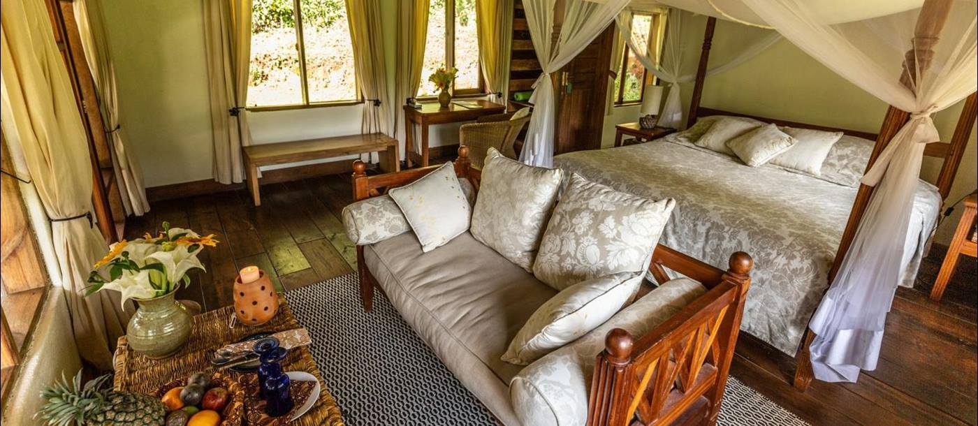 The living are in a bedroom at Bwindi Lodge in Uganda with a couch at the foot of a four poster bed.