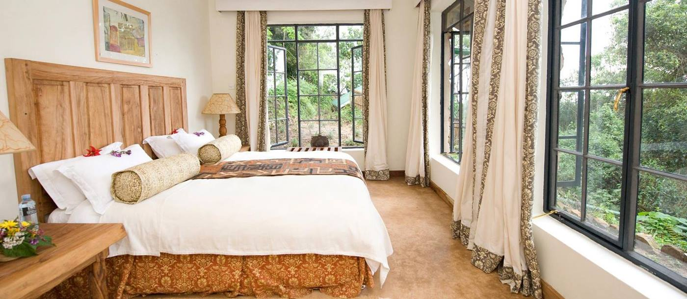 A bedroom with panoramic views from large windows at the foot of the bed at Clouds Mountain Gorilla Lodge in Uganda