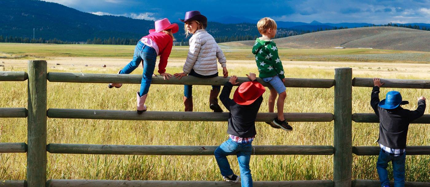Children climbing a fence near Paws Up Ranch, USA