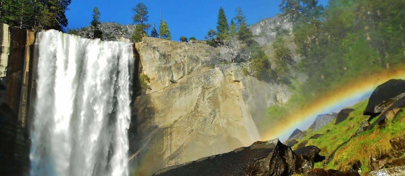 Waterfall and rainbow on a walking trail in Yosemite National Park USA