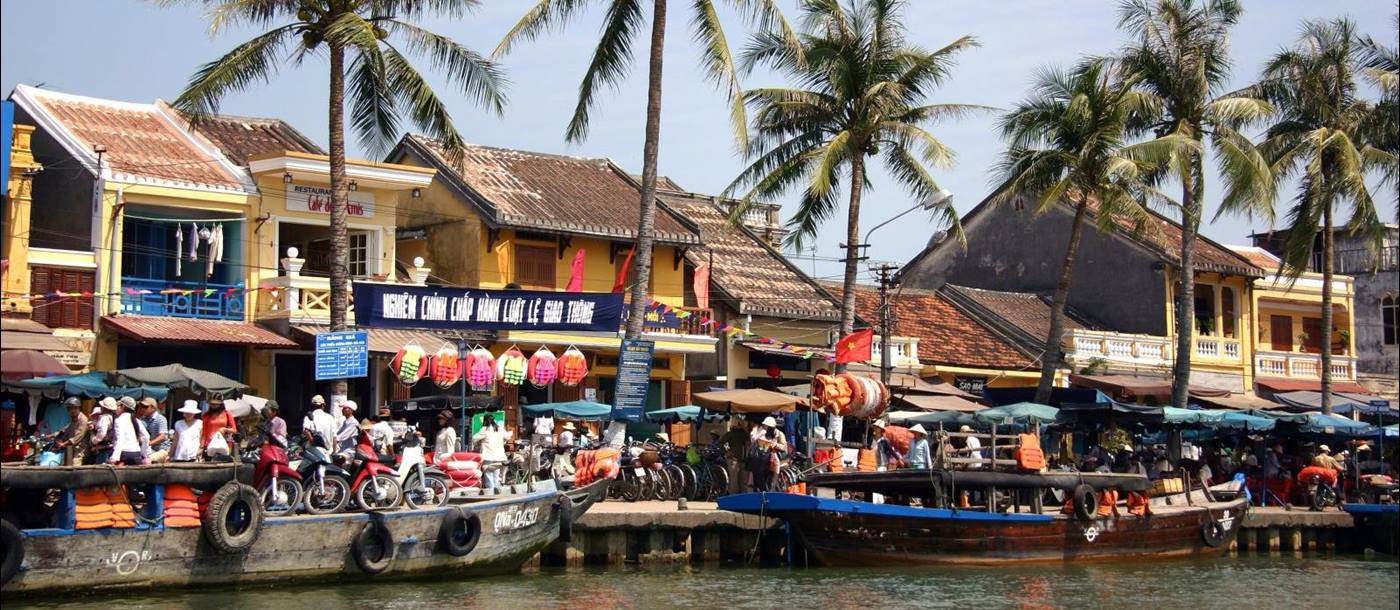 Boats moored along the riverfront in Hoi An with shops behind
