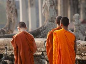 three monks dressed in orange robes at angkor wat