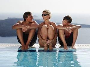 mother sitting between her two sons on the edge of a swimming pool
