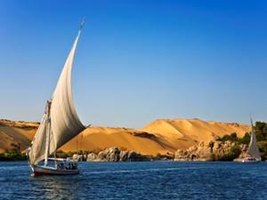boat with white sail sailing down the river nile, egypt