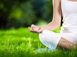 lady dressed in white  sitting in the lotus position on the grass