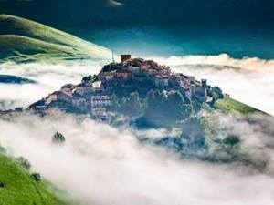 village of castelluccio appearing through the clouds in umbria, italy