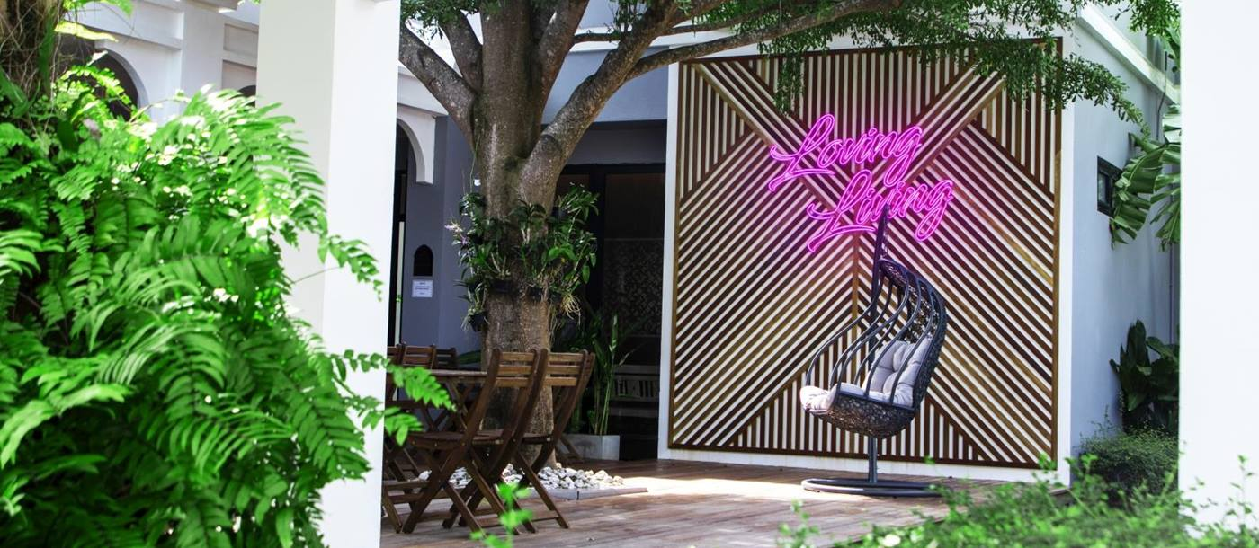 "Terrace seating with a hanging egg chair, a feature wall and a neon sign reading ""Loving Living"" at luxury Zen resort Absolute Sanctuary in Thailand"